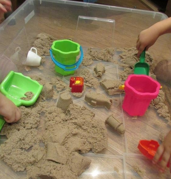 Дети играют в песочнице с генетическим песком
