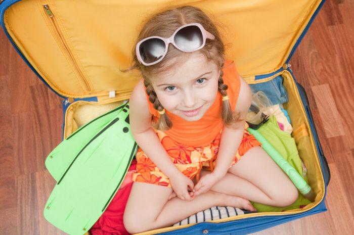 Девочка сидит в чемодане