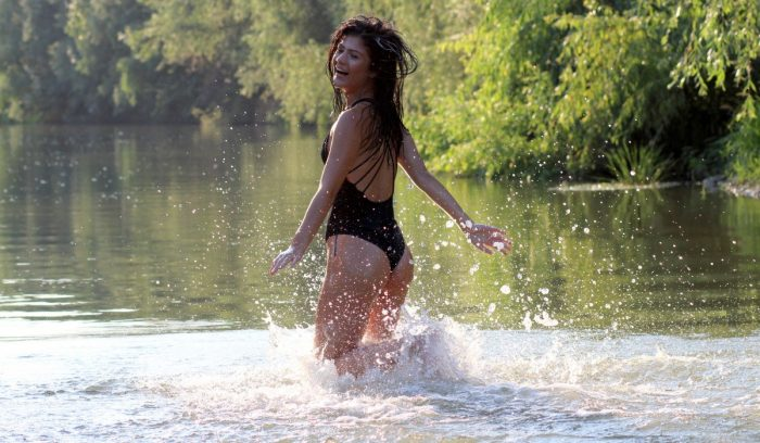 Девушка купается в озере