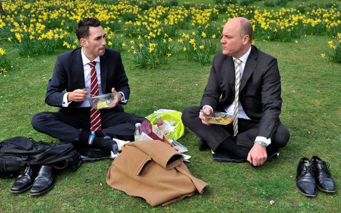Мужчины перекусывают, сидя на траве