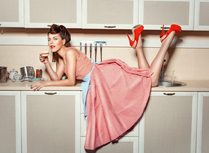 Девушка с пирожным лежит на кухонном столе