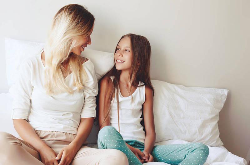 Мама разговаривает с дочкой, сидя на кровати