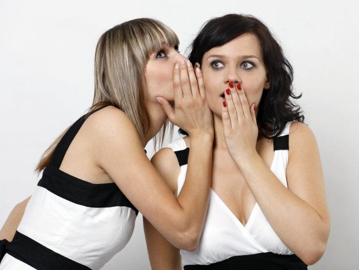 девушка шепчет на ухо подруге