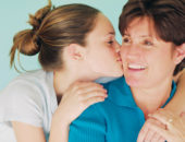 Девочка целует маму