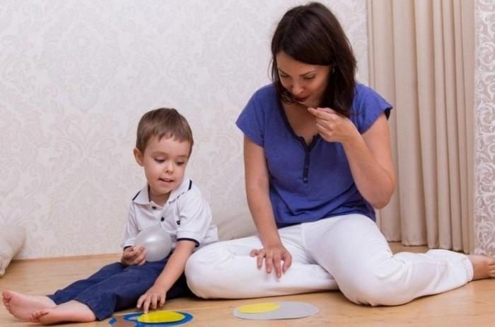 Мама с малышом играет в развивающую игру
